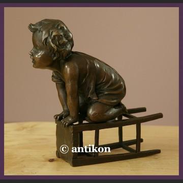 Figurka z brązu słodki malec śliczny brąz chłopiec na stołku sygnowana rzeźba